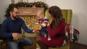 Mutter, Vater und kleines Baby, die im Raum mit Weihnachtsdekoration sitzen Der Mann gibt Mitbringselkasten zu stock footage