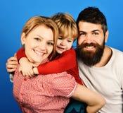 Mutter, Vater und Sohn mit lächelnden Gesichtern umarmen auf Blau stockfoto