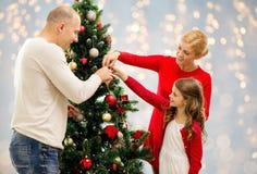 Mutter, Vater und Tochter am Weihnachtsbaum stockfotos