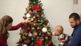 Mutter, Vater und wenig Baby verzierter Weihnachtsbaum Mannholdingkind nahe dem Tannenbaum, helle Dekoration zeigend stock footage