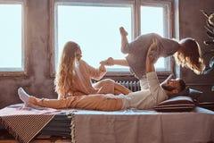 Mutter, Vati und Tochter im Bett Vater, der mit entzückender Tochter im Schlafzimmer spielt stockbild
