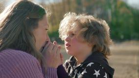 Mutter wärmt ihre Sohn ` s Hände auf dem Strand stock video footage