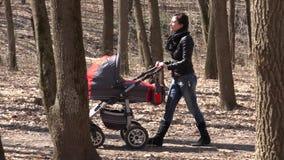 Mutter Walkin im Park mit neugeborenem Kind im Kinderwagen 4K UltraHD, UHD stock video footage