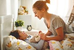 Mutter weckt ihre Tochter im Bett am Morgen auf Stockfotos