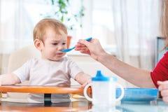 Mutter, welche die Babyholdinghand mit einem Löffel des Breis in der Küche einzieht Gefühle eines Kindes beim Essen der gesunden  lizenzfreie stockfotografie