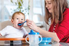 Mutter, welche die Babyholdinghand mit einem Löffel des Breis einzieht Gefühle eines Kindes beim Essen der gesunden Nahrung stockfoto