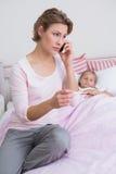Mutter, welche die Temperatur der kranken Tochter nimmt Stockbilder