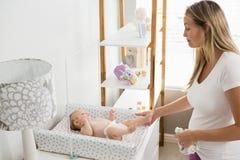 Mutter, welche die Windel ihres Babys ändert Lizenzfreie Stockfotografie