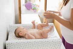 Mutter, welche die Windel ihres Babys ändert Lizenzfreies Stockfoto