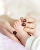 Mutter, welche die Zehe des Babys hält Stockbild