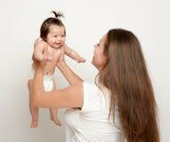 Mutter wirft oben Baby, Spiel und Habenspaß, Parenting, glückliches Familienkonzept Lizenzfreie Stockfotografie