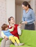 Mutter zahlt Kindermädchen für ihr Kind Lizenzfreies Stockfoto