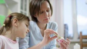 Mutter zeigen ihrer Tochter, wie man Ei mit Scheinen für Feiertag mit einer Bürste verziert stock video