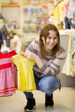 Mutter zeigt Kleider für ihre Tochter - kleines Mädchen im Kinderkleidungsspeicher lizenzfreie stockbilder
