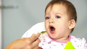 Mutter zieht ein kleines Kind mit einem Löffelvoll Gemüse ein Kind tut nicht wie Gemüse