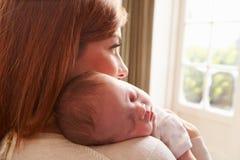 Mutter zu Hause mit schlafender neugeborener Baby-Tochter Stockfotos