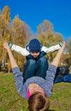 Mutterbabysohn, der Gras außerhalb des Herbstes spielt lizenzfreie stockbilder