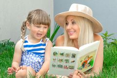 Mutterblondine und -tochter liegen auf dem Gras und lesen ein Buch, glückliche Familie lizenzfreie stockbilder