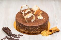 Mutterchokladkaka med kex och muttrar på tabellen royaltyfri foto