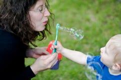 Mutterdurchbrennenluftblasen mit Kleinkind lizenzfreies stockbild
