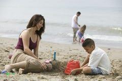 Muttergebäudesandburg mit Sohn auf Strand lizenzfreie stockbilder