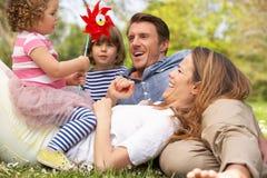Muttergesellschaft, die mit Kindern auf dem Gebiet sitzen Stockfotos