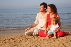 Muttergesellschaft mit dem Kind, das auf Sand auf Küste sitzt Stockfotos