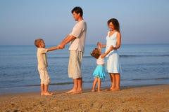 Muttergesellschaft mit den Kindern, die am Rand von Meer stehen Stockbild