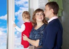 Muttergesellschaft mit einem Kind, welches heraus das Fenster schaut Stockbild
