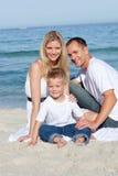 Muttergesellschaft mit ihrem Sohn, der auf dem Sand sitzt stockfotografie
