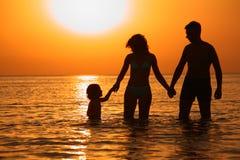 Muttergesellschaft mit Kind im Meer auf Sonnenuntergang Stockbilder