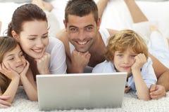 Muttergesellschaft und Kinder im Bett unter Verwendung eines Laptops Stockfoto