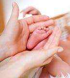 Mutterhände, die Babyfüße halten Stockfotografie