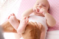 Mutterhände, die nette Babyfüße halten Lizenzfreies Stockfoto