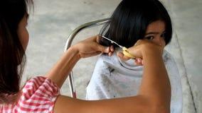 Mutterhaar kleidet ihr Mädchen, Mutter, die Haar ihre Kindertochter kleidet Mädchen stören Mutter schnitt ihr Haar stock video footage