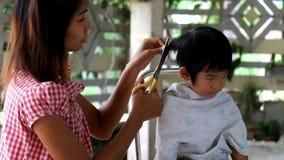 Mutterhaar kleidet ihren Jungen, Mutter, die Haar ihren Kindersohn kleidet Sohn stören Mutter schnitt sein Haar stock video footage