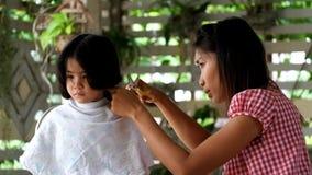 Mutterhaar kleidet ihren Jungen, Mutter, die Haar ihren Kindersohn kleidet Sohn stören Mutter schnitt sein Haar stock video