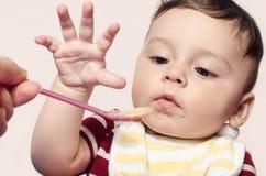 Mutterhand, die Säuglingssäuglingsnahrung einzieht Kind, das versucht, den Löffel zu ergreifen Lizenzfreies Stockbild