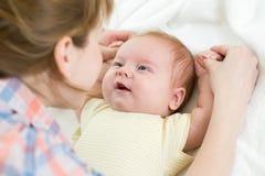 Mutterhandeln gymnastisch zum Baby Stockfotos