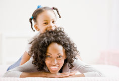 Mutterlagen auf Bett mit spielerischer Tochter Lizenzfreie Stockbilder