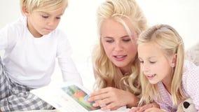 Mutterlesegeschichte zu ihrem Kind zwei stock video