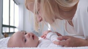Mutterliebe, junges Elternteil leicht berührt und küsst ihr entzückendes Baby, das auf ändernder Tabelle liegt stock footage