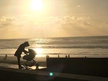 Mutterliebe mit kleinem Kind im Kinderwagen auf dem Strand mit romantischem Sonnenuntergang lizenzfreie stockbilder