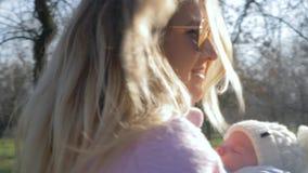 Mutterschaft, attraktive Mutter mit schlafendem Kind im Riemen geht draußen am sonnigen Tag stock footage