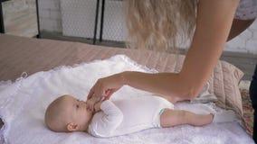 Mutterschaft, Elternteil spielt mit Babytochter, die auf dem Bett liegt und ihre Finger zu Hause bitting stock footage