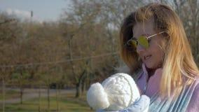 Mutterschaft, junge Mutter in der Sonnenbrille Lied für Baby im Riemen in Park singend stock video footage