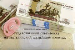Mutterschaftskapital- und Babyattrappe mit Rollen des Geldes Stockfotografie