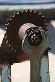 Mutterskiftnyckel och rostigt kugghjul arkivbilder