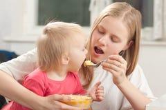 Mutterspeisentochter mit Brei Stockfotos