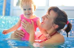 Mutterspiel mit ihrem Kind im Schwimmbad Stockfotos